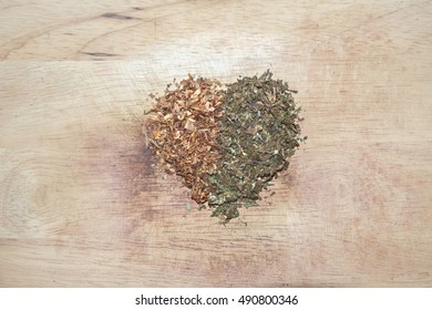 Marijuana and tobacco on wood background, shaped heart.