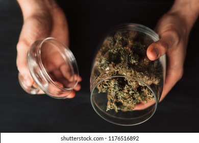 A lot of marijuana. Top view. Close up. Black background. Concepts of legalizing weed. A bank with fresh buds of cannabis in the hands of a man.