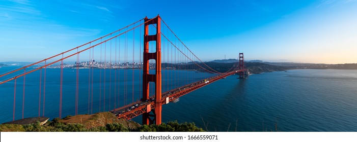 Marin, CA—Feb 19, 2020; Panorama view of the red steel Golden Gate suspension bridge from the north side crossing of San Francisco Bay at sunset from Golden Gate National Recreation Area