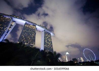 Marina Bay area, Singapore, February 3, 2018: Beautiful lights lit up from windows of Marina Sands Hotel and from the distant Singapore Flyer Ferris wheel with white clouds as background