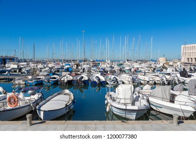 marina bay with yachts, vessels, sailboats and other ships in Livorno, Italy. Sunny day with blue sky and sea water.