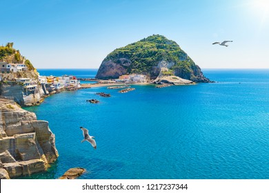 Marina with boats, small beach, cafes and hotels, giant green rock near Sant'Angelo on Ischia island, Italy. Sant'Angelo is small village within comune of Serrara Fontana, Ischia.