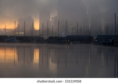 Marina and buildings in downtown Vancouver just visible through early morning fog