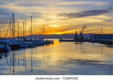 Marina and commercial harbor of Vilagarcia de Arousa at cloudy and colorful sunset