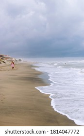 Marina di Ardea, Rome, Italy - 30/08/2020: Woman walking alone on the empty beach with stormy sea at the end of summer. Italian beaches become empty at the end of August.