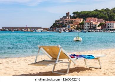 MARINA DI CAMPO, ISOLA ELBA, ITALY - SEPTEMBER 16, 2018: Beach of the town Marina di Campo end emerald sea of Elba Island. Tuscany, Italy.