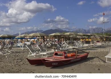 MARINA DI MASSA, ITALY - AUGUST 17 2015: Bathing establishment in Marina di Massa, with rowing life boat overlooking the Apuan Alps