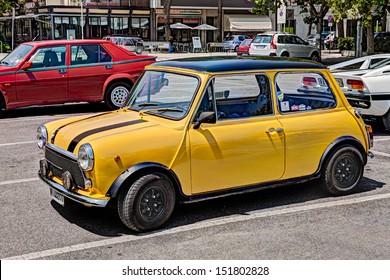 "MARINA DI RAVENNA, ITALY - JULY 14, 2013: a yellow vintage car Mini Cooper 1300 at rally of classic cars ""Raduno day"" on July 14, 2013 in Marina d Ravenna, Italy"