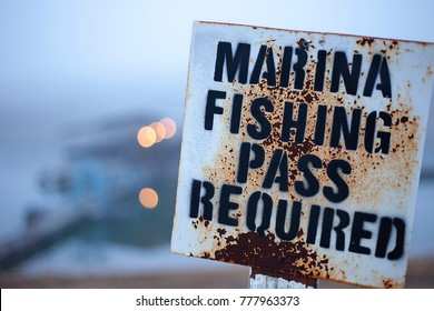 Marina fishing pass. Rusty sign w/ pier in the background blurred