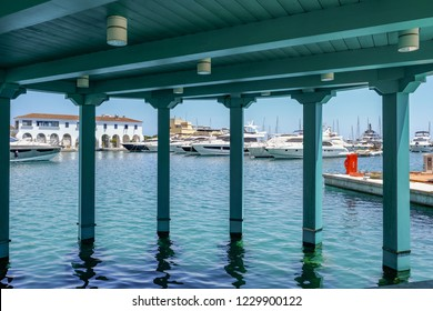 Marina, Limassol, Cyprus - June 14, 2018: Luxury motor boats, cruisers and yatchs lined up in the marina. Seen through the struts of a wooden structure.
