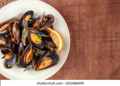 Marinara mussels, moules mariniere, close-up overhead shot on a dark rustic wooden background with copy space
