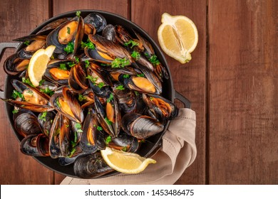 Marinara mussels, moules mariniere, with lemon slices, in a cooking pot, shot from the top on a dark rustic wooden background with copy space