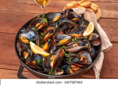 Marinara mussels, moules mariniere, with toasted bread, lemon slices, and wine on a dark rustic wooden background