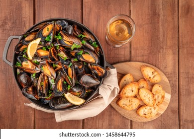 Marinara mussels, moules mariniere, with toasted bread and white wine, in a cooking pot, shot from above on a dark rustic wooden background with a place for text
