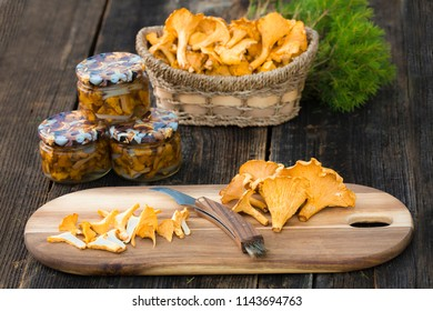 Marinated chanterelle mushrooms in glass jar on rustic background. Selective focus, space for text.