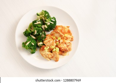 marinated chicken breast fillet with spring onions and broccoli with almond sticks, healthy meal wion a plate and on a white painted table, copy space, high angle view from above