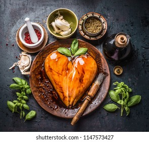 Marinated chicken breast meat in heart shape with rub brush for cooking or grill on rustic dark background with ingredients bowls: herbs, spices and sauce, top view . Protein fitness and diet food