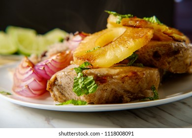 Marinated Cuban pineapple pork chops with traditional black bean rice grilled red onion and fried plantain chips