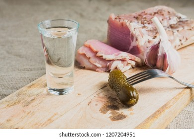Marinated cucumber on a fork, a glass of vodka, sliced fat on a board - Ukrainian snack