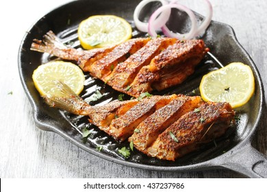 Marinated fried fish / Spicy  fish fry with spices n lemon juice on iron skillet griddle, selective focus