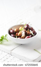 Marinated green and kalamata olives with fresh rosemary in a small bowl. Concept for a tasty and healthy appetizer.