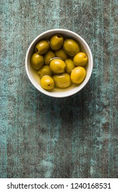 Marinated green olives in bowl. Top view.
