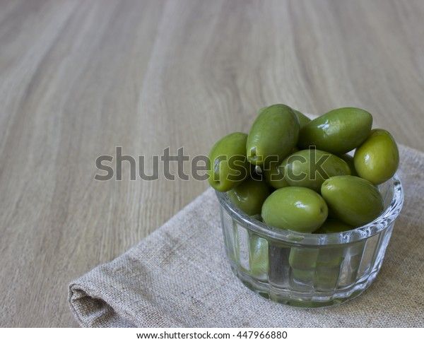 Marinated green olives in glass bowl  on the wooden board