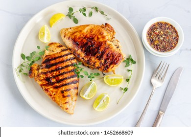 Marinated grilled healthy chicken breasts in a White Plate and served with fresh Oregano on White Background.