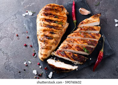 Marinated grilled healthy chicken breasts on a stone board,