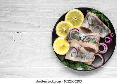 marinated herring fillet with pepper, herbs, onion and lemon on black plate on white background. top view with copy space. healthy food
