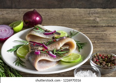 marinated herring fillet with pepper, rosemary, onion and lime in a plate on rustic wooden background. close up. healthy food