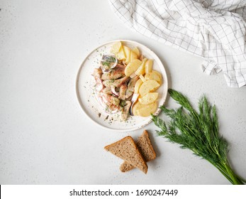Marinated Herring fish with potatoes slices and red onion, rye bread on the white table. Top view