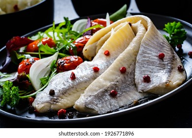 Marinated herrings with roast cherry tomatoes and fresh vegetable leaves on black table