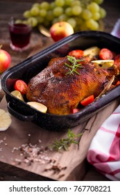 Marinated homemade roasted duck with herbs, grapes, garlic and apples served in a rustic style served in a rustic style.