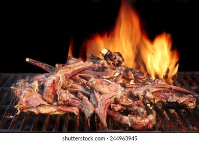 Marinated Lamb Ribs in BBQ Souse on the Hot Grill. Flame of Fire on the Black Background