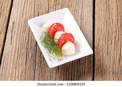 Marinated mozzarella cheese balls and fresh tomato