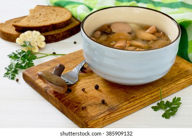 Marinated mushrooms boletus served with bread in rustic style