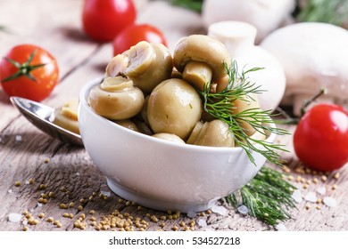 Marinated mushrooms, vintage wooden background, selective focus