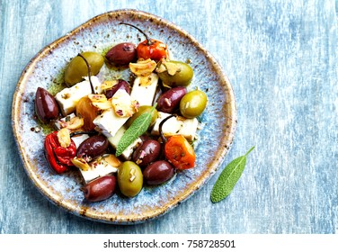 Marinated olives, habanero peppers and feta cheese on a plate. Home made food. Concept for a tasty appetizer. Top view. Copy space.