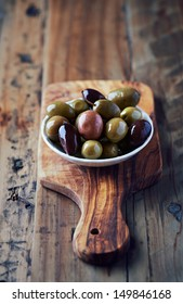 Marinated olives in a small ceramic bowl. Organic kalamata and green olives. Symbolic image. Concept for a tasty and healthy appetizer. Rustic wooden background. Close up.