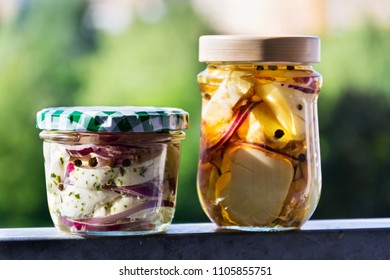 Marinated pickled cheese in oil with black pepper, onions, herbs and spices in glass jar