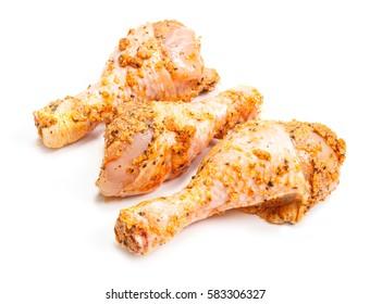 Marinated raw chicken drumsticks on white background