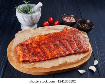 Marinated raw pork spare ribs on crumpled paper on a bamboo cutting board, with rosemary twigs, tomatoes, garlic cloves, pepper corns and coarse pink salt