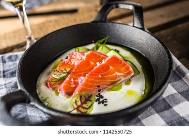 Marinated salmon with cream cucumber and dill in pan with aperitif. Culinary serving of meal in restaurant.