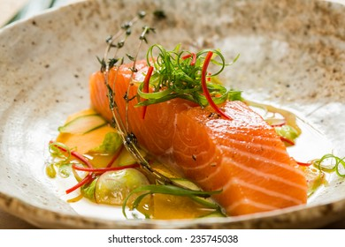 Marinated salmon with green salad and spices.  Shallow dof.