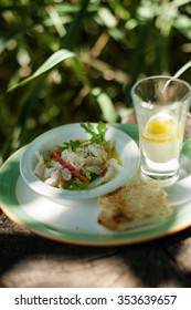 Marinated seafood on a plate with bread, on a background of straw hat