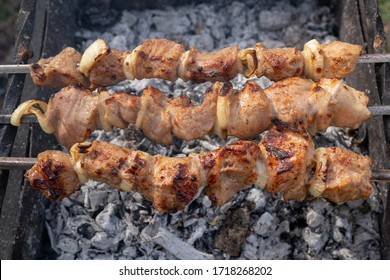 Marinated shashlik preparing on a barbecue grill over charcoal. Kebap on the grill restaurant for dinner. Juicy meat on coals. Traditional Russian and Oriental cuisine. May holidays in Russia picnic