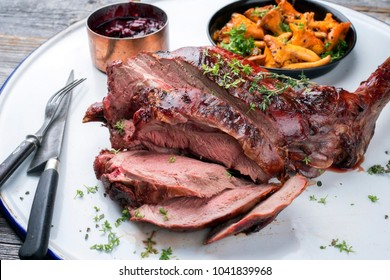 Marinated sliced barbecue aged leg of venison with chanterelles and cherry sauce as top view on rustic background