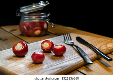 Marinated small red peppers stuffed goat cheese on wooden table