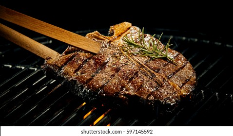 Marinated spicy lean t-bone steak grilling on a BBQ flavored with a sprig of fresh rosemary being lifted off the fire with a pair of wooden tongs